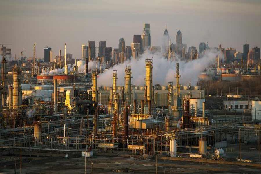 The Philadelphia Energy Solutions oil refinery owned by The Carlyle Group is seen at sunset in front of the Philadelphia skyline. 	— Reuters