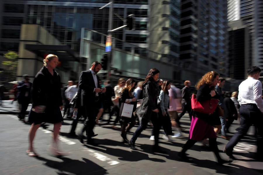 Office workers and shoppers walk through Sydney's central business district in Australia. — Reuters