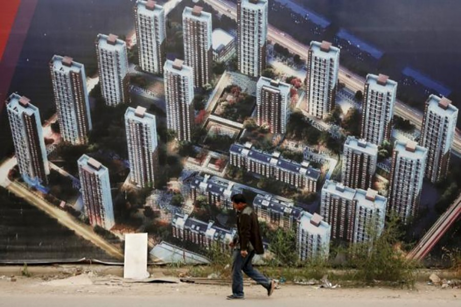 A man walks past a wall at a construction site for a new residential compound at the Binhai new district in Tianjin, China, October 18, 2015. (Reuters)