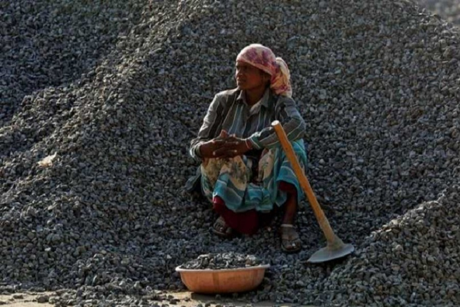 A woman labourer rests on a pile of stones at a construction site, in Mumbai, India March 16, 2017. Reuters/File Photo