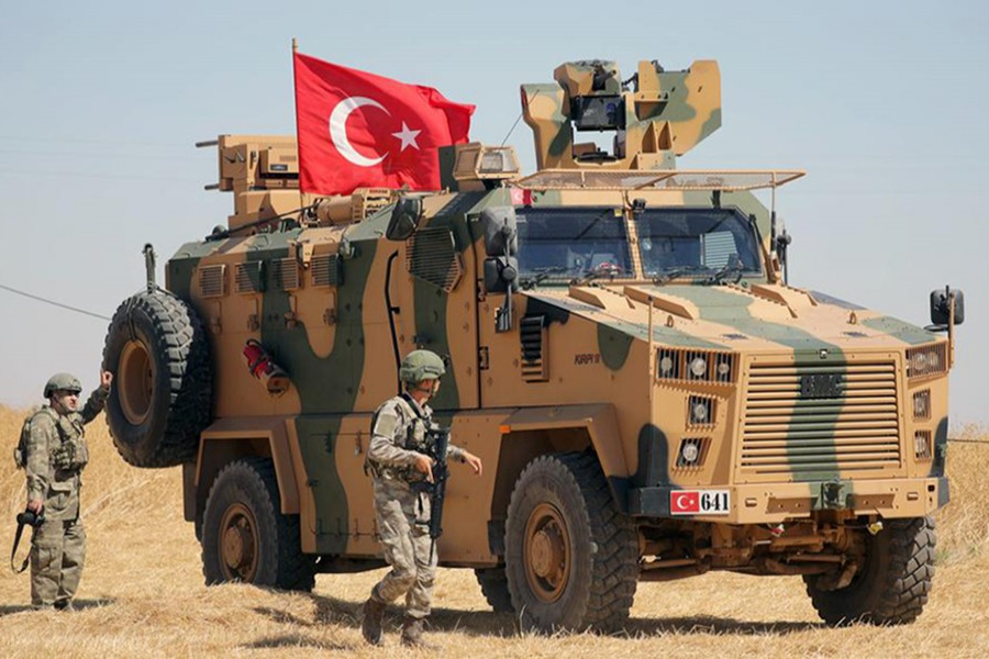 A Turkish soldier walks next to a Turkish military vehicle during a joint US-Turkey patrol, near Tel Abyad, Syria on September 8, 2019 — Reuters/Files