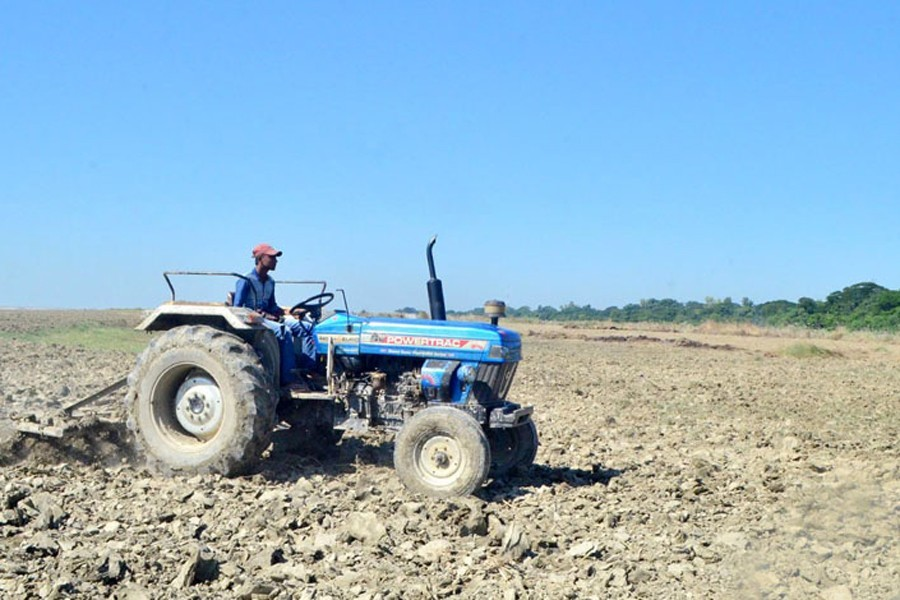 Representational image: A farmer is ploughing a piece of land by a tractor in Godagari upazila of Rajshahi, November 09, 2020. — FE Photo