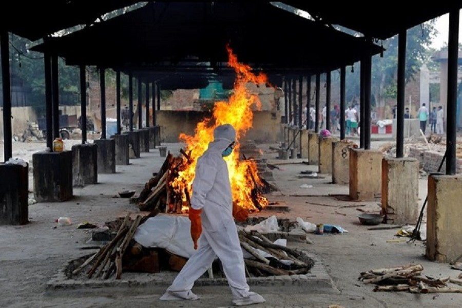 A priest wearing personal protective equipment (PPE) walks in front of the body of a person who died of the coronavirus disease (Covid-19), as he collects woods to make a funeral pyre at a crematorium in New Delhi, India, July 03, 2020 — Reuters