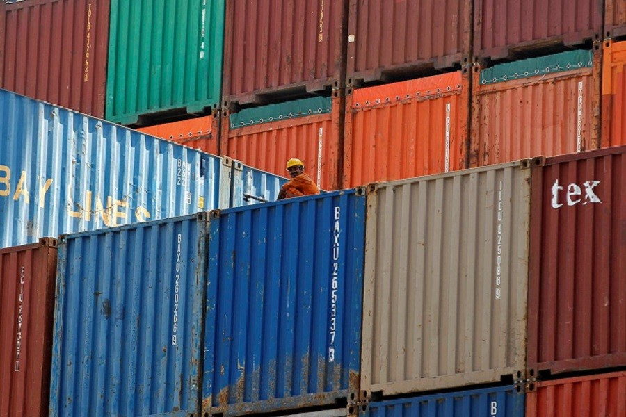 A worker sits on a ship carrying containers at Mundra Port in the western Indian state of Gujarat April 01, 2014 — Reuters/Files