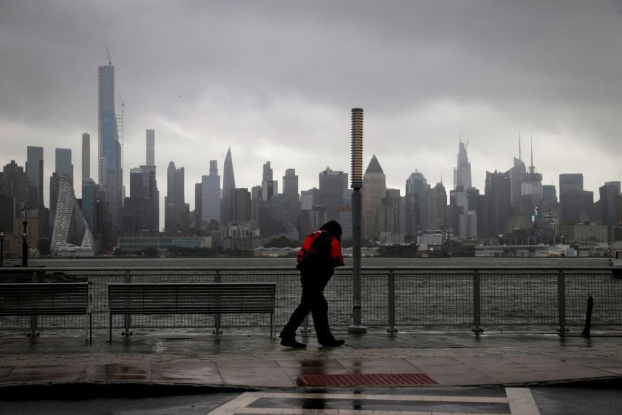 A man walks into heavy wind and rain along the waterfront of the Hudson River in front of the New York City skyline during Tropical Storm Isaias in Weehawken, New Jersey, US, August 4, 2020. REUTERS/Mike Sega