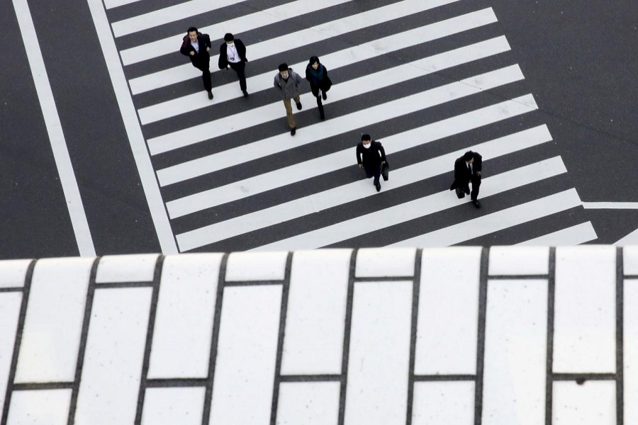 People cross a street in a business district in Tokyo, Japan, February 16, 2016 — Reuters/Files