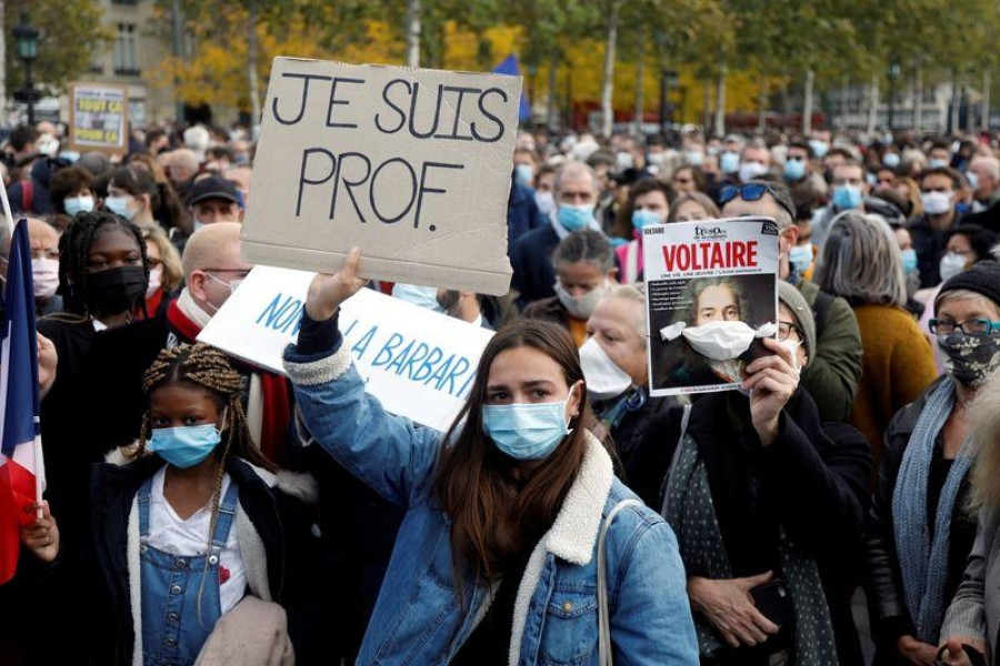 """People gather at the Place de la Republique in Paris, to pay tribute to Samuel Paty, the French teacher who was beheaded on the streets of the Paris suburb of Conflans-Sainte-Honorine, France, October 18, 2020. Placard reads """"I am a teacher"""". REUTERS/Charles Platiau"""