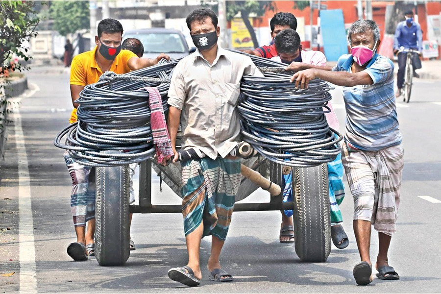 Labourers wearing face masks carry iron rods by a push-cart, as the coronavirus (Covid-19) outbreak continues, at Tejgaon in Dhaka city, June 27, 2020 — FE photo by Shafiqul Alam
