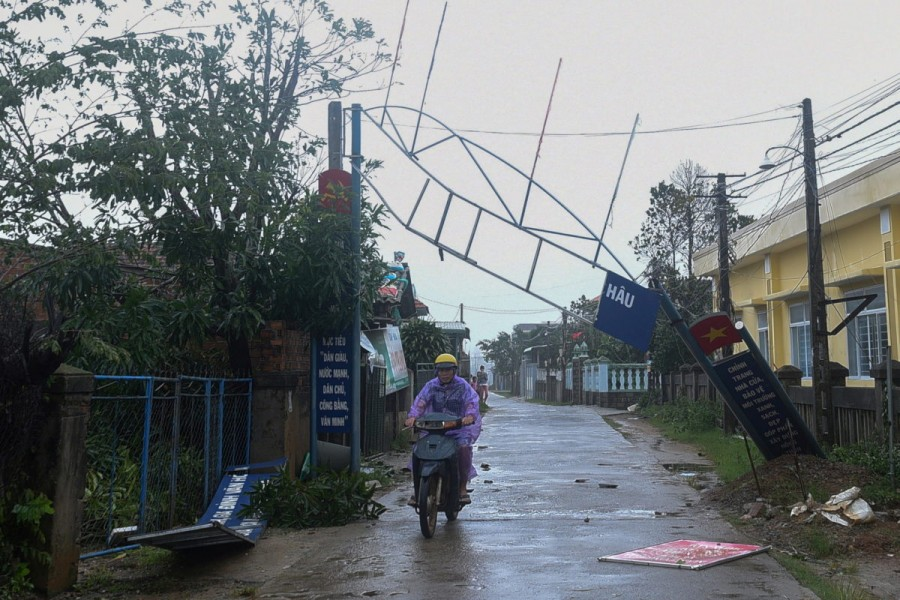A man bikes past a broken sign as the Typhoon Molave lashes Vietnam's coast in Binh Chau village, Quang Ngai province October 28, 2020. REUTERS/Thanh Hue