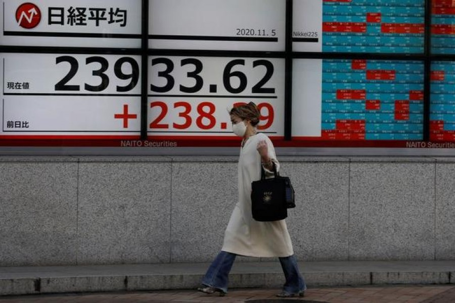 A woman wearing a protective mask, following the coronavirus disease (Covid-19) outbreak, walks past a screen showing Nikkei index outside a brokerage in Tokyo, Japan on November 5, 2020 — Reuters/Files