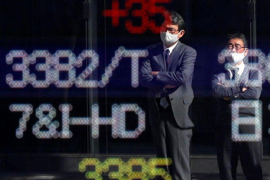 Passersby wearing protective face masks are reflected on a stock quotation board outside a brokerage, in Tokyo, Japan on November 10, 2020 — Reuters/Files