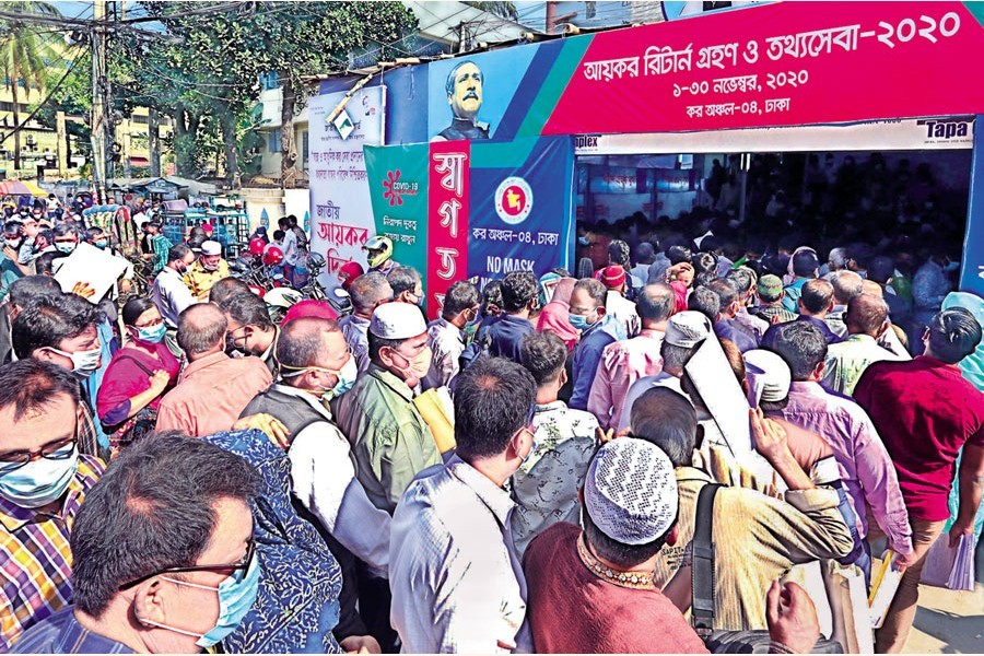 Ignoring social distancing norms, taxpayers wait in long queues to file income tax returns at the Tax Zone-4 at Bijoynagar in the city on Sunday — FE photo