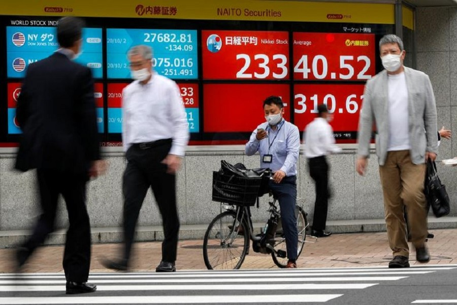 Passersby wearing protective face masks walk past a screen displaying Nikkei share average and world stock indexes outside a brokerage, amid the coronavirus disease (Covid-19) outbreak, in Tokyo, Japan October 5, 2020 — Reuters/Files
