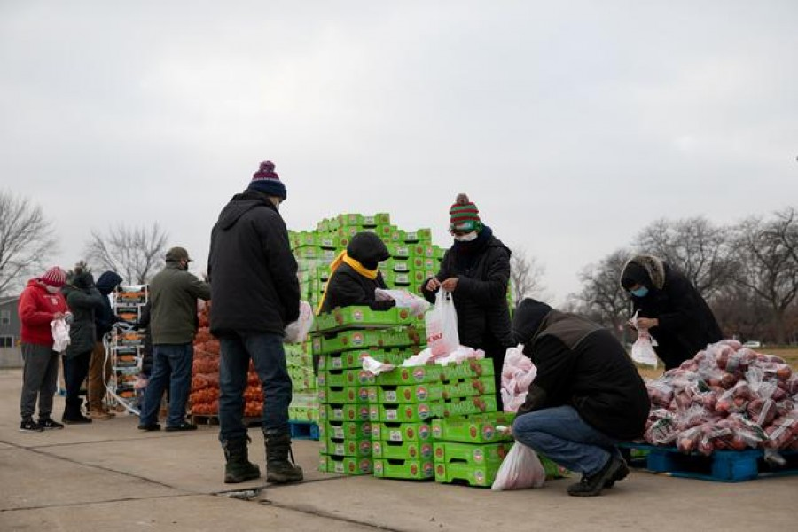Volunteers from Forgotten Harvest food bank sort and separate different goods before a mobile pantry distribution ahead of Christmas, amid the coronavirus disease (COVID-19) pandemic in Warren, Michigan, US, December 21, 2020. REUTERS/Emily Elconin/File Photo