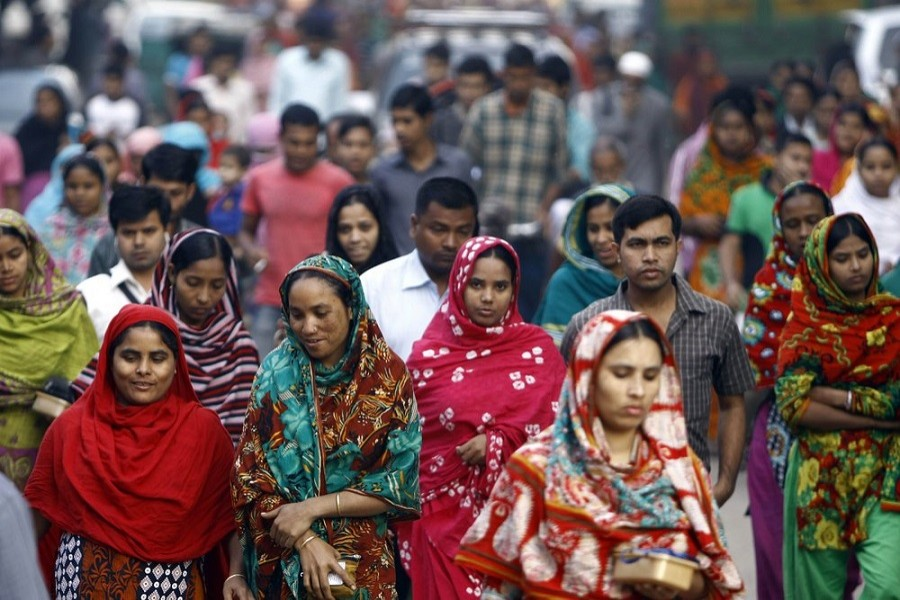 In this Feb 13, 2014 file photo, Bangladeshi garment workers arrive for work early morning in Dhaka, Bangladesh — AP Photo