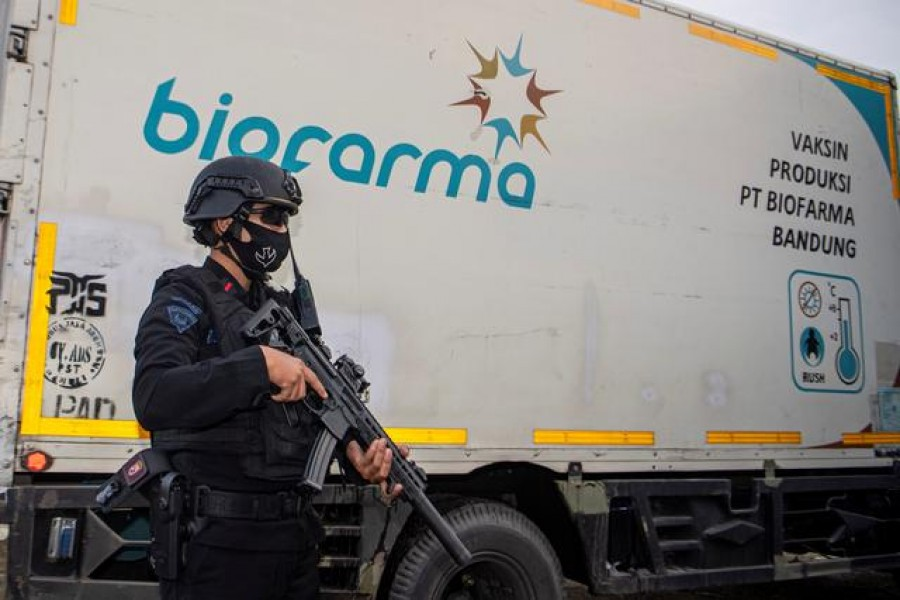 An armed police officer stands guard next to a truck containing Sinovac's vaccine for coronavirus disease (Covid-19) as it arrives at the cold room of Indonesia's local health department in Palembang, South Sumatra province, Indonesia, January 4, 2021 — Antara Foto/Nova Wahyudi/ via Reuters