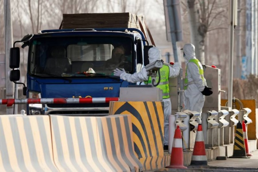 FILE PHOTO: Police officers in PPE stop a car coming from Hebei province at a checkpoint, following the coronavirus disease (COVID-19) outbreak, on the outskirts of Beijing, China January 12, 2021. REUTERS