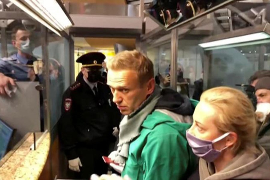 A still image taken from video footage shows law enforcement officers speaking with Russian opposition leader Alexei Navalny before leading him away at Sheremetyevo airport in Moscow, Russia on January 17, 2021 — Reuters photo
