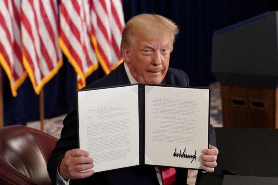 US President Donald Trump shows signed executive orders for economic relief at his golf resort in Bedminster, New Jersey, U.S., August 8, 2020. REUTERS/Joshua Roberts/File Photo