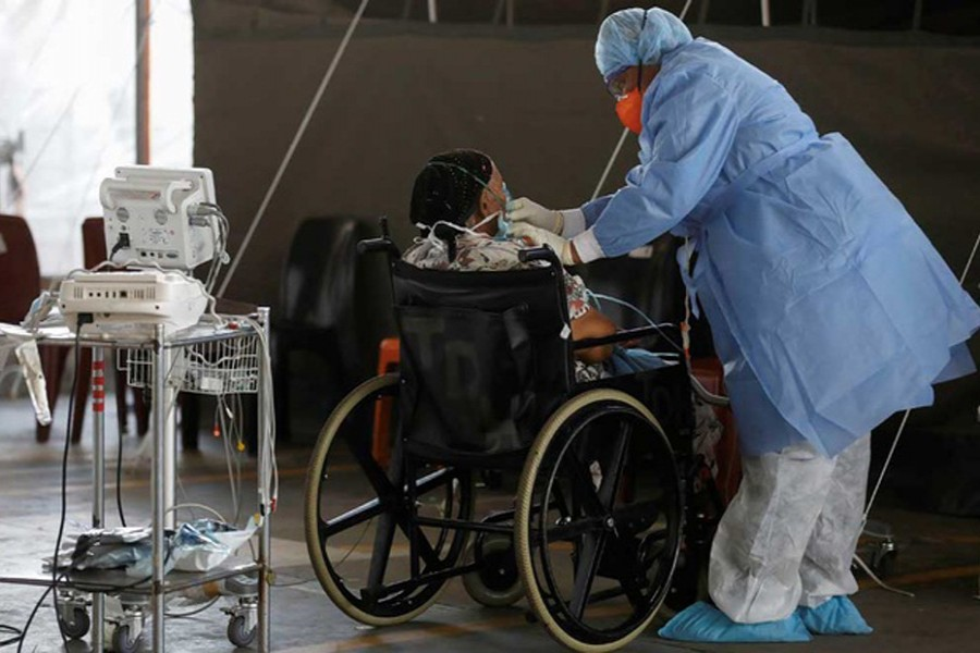 Healthcare workers tend to a patient at a temporary ward set up during the coronavirus disease (COVID-19) outbreak, at Steve Biko Academic Hospital in Pretoria, South Africa, Jan 19, 2021. REUTERS