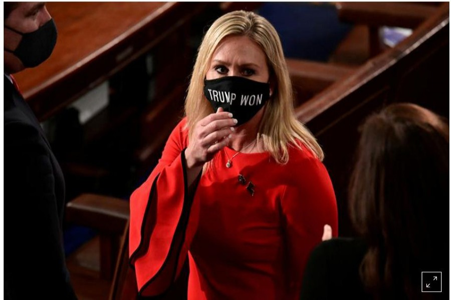 "FILE PHOTO: US Rep. Marjorie Taylor Greene (R-GA) wears a ""Trump Won"" face mask as she arrives on the floor of the House to take her oath of office as a newly elected member of the 117th House of Representatives in Washington, U.S., January 3, 2021. REUTERS/Erin Scott/Pool/File Photo"