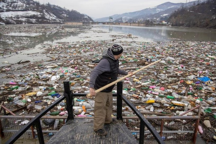 A worker collects plastic trash that litters the polluted Potpecko Lake near a dam's hydroelectric plant near the town of Priboj, Serbia on January 29, 2021 — Reuters photo