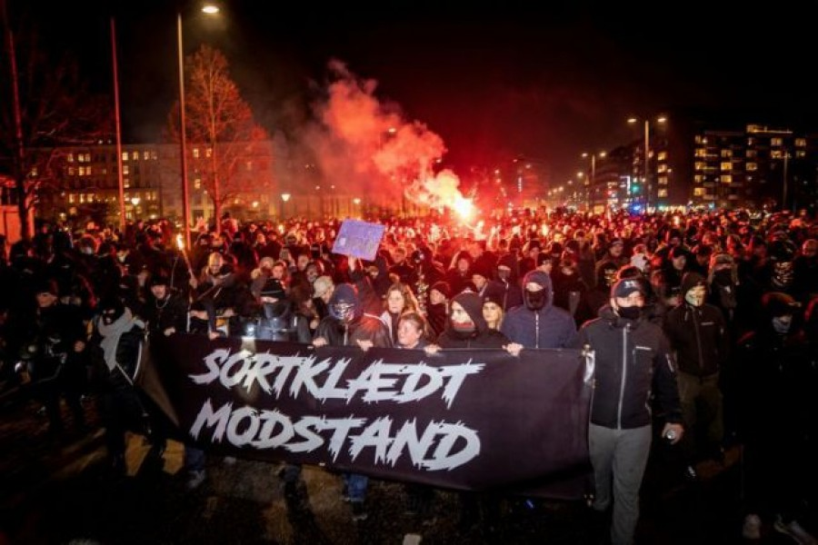 """Demonstrators hold a banner reading """"Black-clad resistance"""" during a protest by a group called Men in Black against Covid-19 restrictions in Copenhagen, Denmark on January 23, 2021  — Mads Claus Rasmussen via REUTERS"""