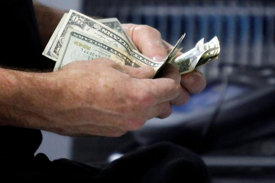FILE PHOTO: A customer counts his cash at the register while purchasing an item at a Best Buy store in Flushing, New York March 27, 2010 - Reuters