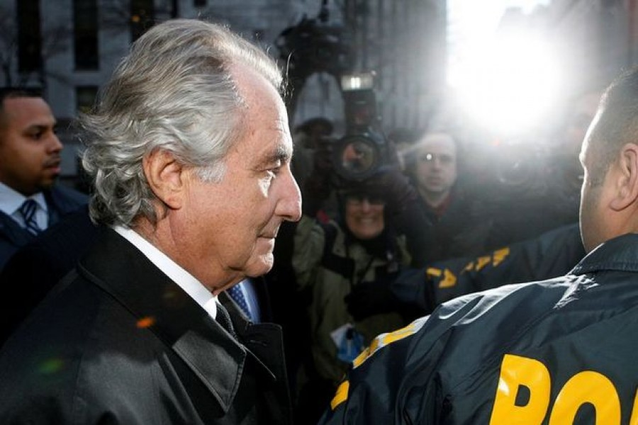FILE PHOTO: Disgraced financier Bernard Madoff is escorted by police and photographed by the media as he departs U.S. Federal Court after a hearing in New York, January 5, 2009. REUTERS/Lucas Jackson/File Photo