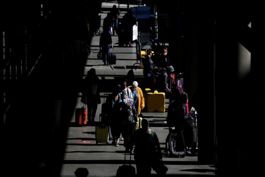 Travellers walk through a pick-up area in the arrivals section at Seattle-Tacoma International Airport in SeaTac, Washington, US, April 12, 2021 — Reuters/Files