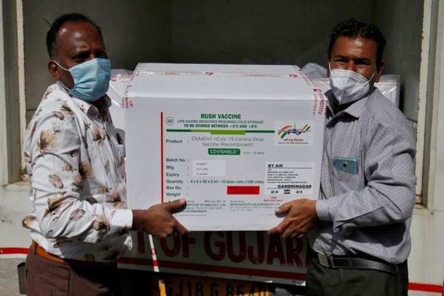 Officials unload boxes containing vials of AstraZeneca's COVISHIELD, a coronavirus disease (COVID-19) vaccine manufactured by Serum Institute of India, outside a vaccination storage centre in Ahmedabad, India, January 12, 2021. REUTERS