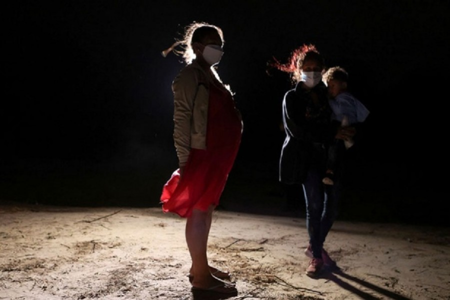 A pregnant asylum-seeking woman stands on the American side after crossing on an inflatable raft the Rio Grande river from Mexico, in Roma, Texas, US, April 22, 2021. Reuters