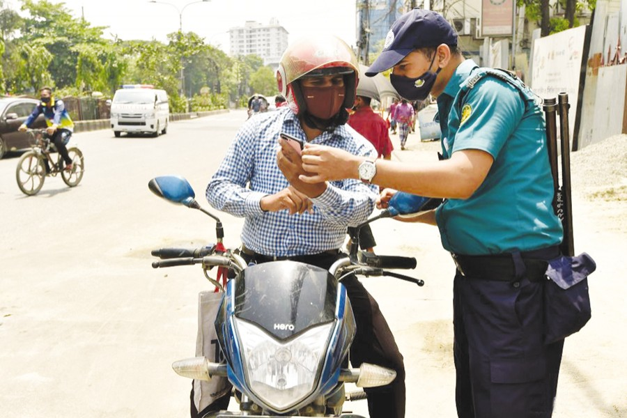 A policeman checks a man's movement pass during a lockdown to curb the spread of Covid-19 in Dhaka on April 14 —Xinhua Photo