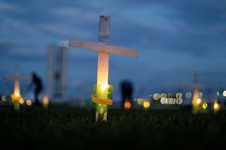 A candle and cross symbolising the ones who died from the coronavirus disease (COVID-19) are seen in front of the National Congress in Brasilia, Brazil Apr 27, 2021. REUTERS