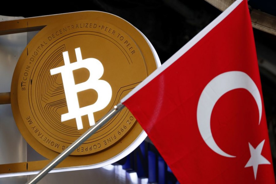 A bitcoin logo is seen next to Turkish flag at a cryptocurrency exchange shop in Istanbul, Turkey April 27, 2021. Picture taken April 27, 2021. REUTERS/Murad Sezer