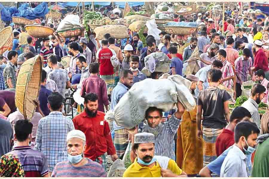 NO COVID-19 FEAR: Sellers and buyers going about their business at Karwan Bazar kitchen market in the city on Tuesday, paying no heed to mask mandate or social distancing norms — FE photo by KAZ Sumon