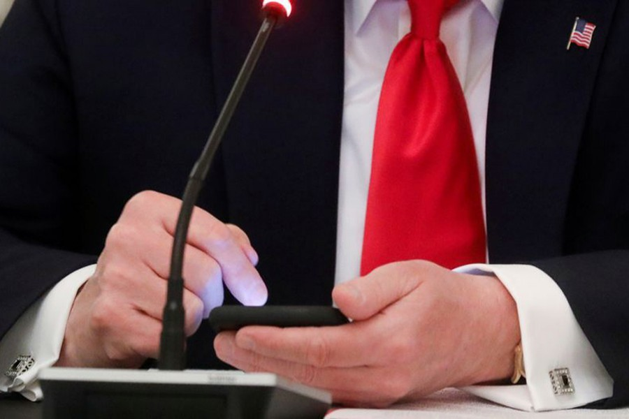 Former US President Donald Trump taps the screen on a mobile phone in the State Dining Room at the White House in Washington, US — Reuters/Files