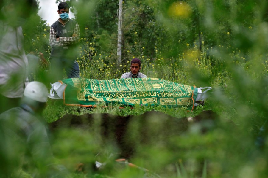 Relatives are seen next to the body of a man who died due to the coronavirus disease (Covid-19), as they wait for a grave to be prepared for his burial at a graveyard on the outskirts of Srinagar on May 4, 2021 — Reuters photo