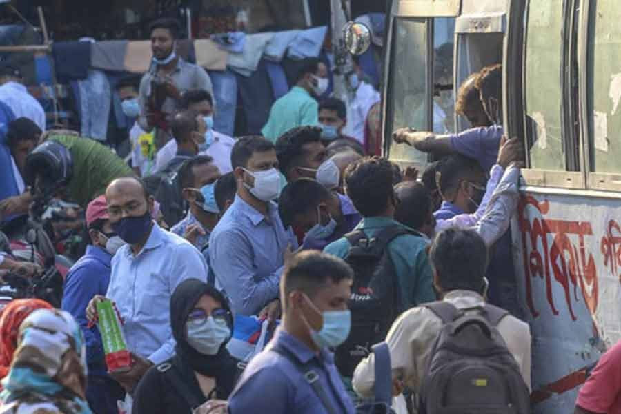 Passengers scramble to get on a bus in Dhaka on the first day of resumption of intra-city public transport services amid a coronavirus outbreak on Thursday -bdnews24.com photo