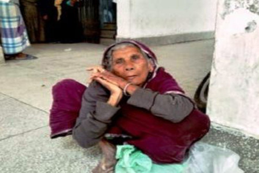 Moriomjan, a 100-year old woman, waited on the Deputy Commissioner office's corridor in Chandpur Sadar on Thursday morning with a govt slip in hand in the hope of getting relief rice — FE Photo