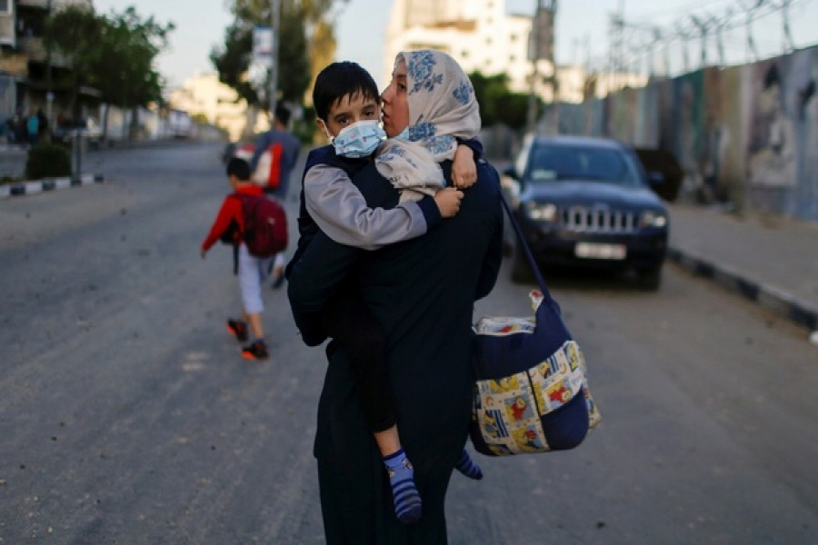 A Palestinian woman carrying her son evacuates after their tower building was hit by Israeli airstrikes, amid a flare-up of Israeli-Palestinian violence, in Gaza City, May 12, 2021 - Reuters photo