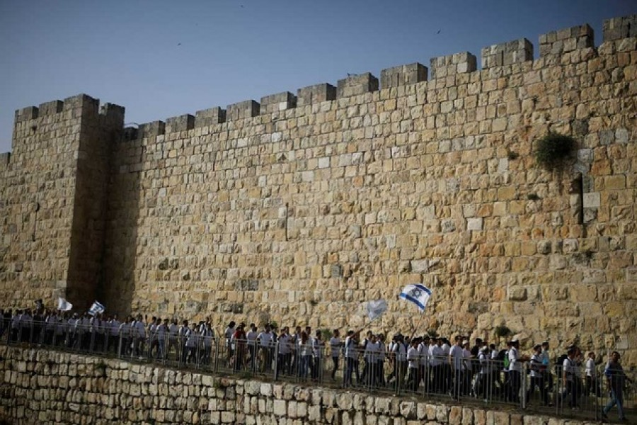 Youths wave Israeli flags during a parade marking Jerusalem Day amid Israeli-Palestinian tension as they march along the walls surrounding Jerusalem's Old City, May 10, 2021. REUTERS