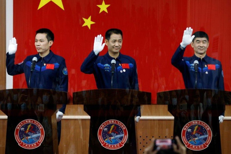 Chinese astronauts Nie Haisheng, Liu Boming, and Tang Hongbo wave as they meet members of the media behind a glass wall before the Shenzhou-12 mission to build China's space station, at Jiuquan Satellite Launch Center near Jiuquan, Gansu province, China on June 16, 2021 — Reuters photo