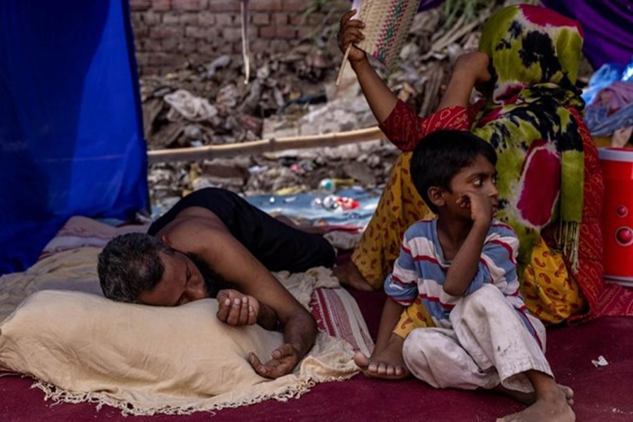 A Rohingya refugee family rests in a temporary shelter after a fire destroyed a Rohingya refugee camp on Saturday night, in New Delhi, India on June 14, 2021 — Reuters/Files