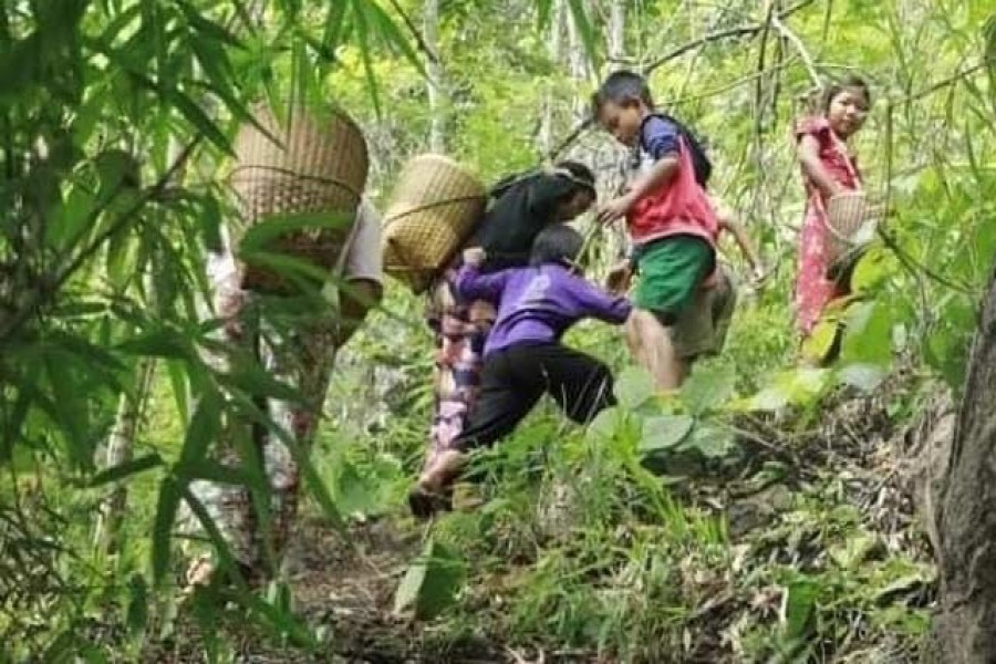 People displaced by fighting in eastern Myanmar climb through forest in Kayah State, May 26, 2021 — Reuters