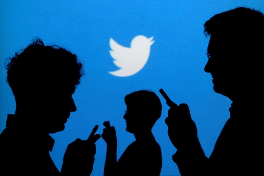 People holding mobile phones are silhouetted against a backdrop projected with the Twitter logo in this illustration picture taken September 27, 2013 — Reuters