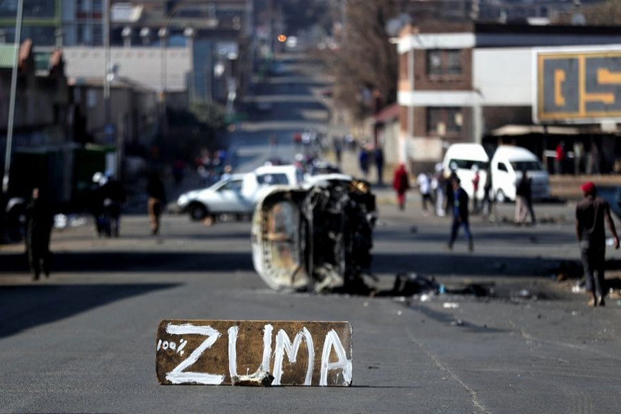 The remains of a burnt car and a sign block the road after stick-wielding protesters marched through the streets, as violence following the jailing of former South African President Jacob Zuma spread to the country's main economic hub in Johannesburg, South Africa on July 11, 2021 — Reuters photo