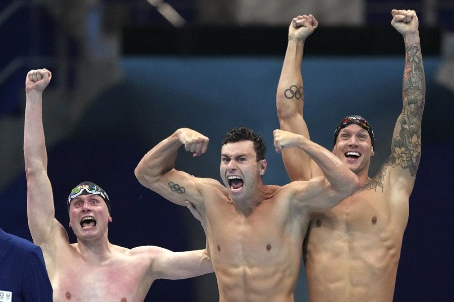 United States men's 4x100m freestyle relay team Bowen Beck, Blake Pieroni, and Caeleb Dressel celebrate after winning the gold medal at the 2020 Summer Olympics, Monday, July 26, 2021, in Tokyo, Japan — AP Photo/Matthias Schrader