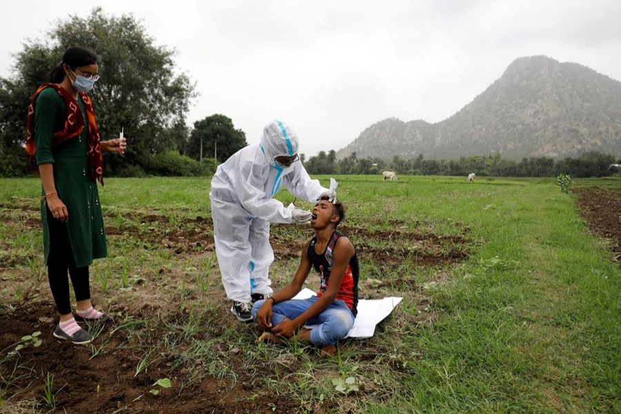 Healthcare worker Hemaben Raval collects a swab for a rapid antigen test from farmer Vinod Vajabhai Dabhi in his field, during a door-to-door vaccination drive amid the ongoing coronavirus disease (Covid-19) outbreak in Banaskantha district in the western state of Gujarat, India on July 23, 2021 — Reuters/Files