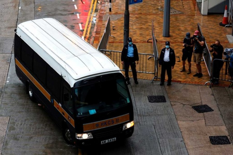 A prison van arrives as police stand guard for Tong Ying-kit's arrival, the first person charged under a new national security law, in Hong Kong, China, July 30, 2021. REUTERS